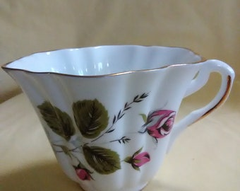 Vintage tea cup. Fine bone China. Pink rose design on both sides, but different. Made in England.