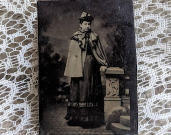 Antique Victorian Tintype photograph of a very fashionable cape wearing young lady in full attire