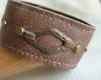 Stamped brass on light brown leather cuff