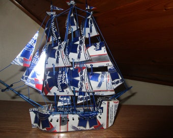 Pasbst Blue Ribbon ship made from 12 recycled aluminum cans rry outs for ten cents a can.