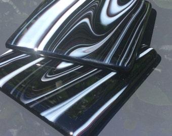 Set of two sleek black fused glass coasters.