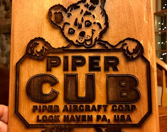 Piper Cub logo deeply Engraved into a solid pine board