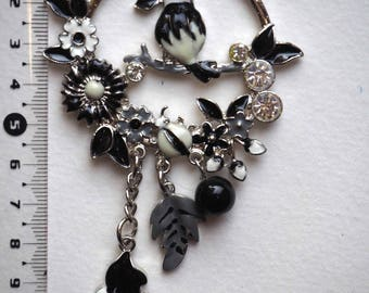 Beautiful pendant black and white parrot on branch surrounded by flowers with charms