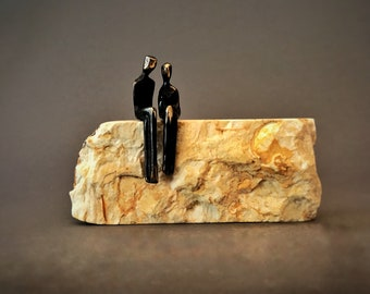 Tiny miniature sculpture of a loving couple sitting on a rock | he is proposing marriage to his girlfriend | they are to be engaged