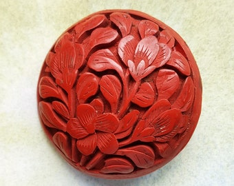 A large and lovely Chinese floral carved cinnabar button. Probably 1920s. About 3.2 cms.