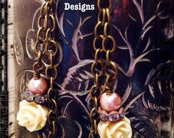 Dangley, Earrings, Cream toned flowers, Antiqued brass chains, w/ Vintage Chandelier crystals. By: Kari Wolf Designs