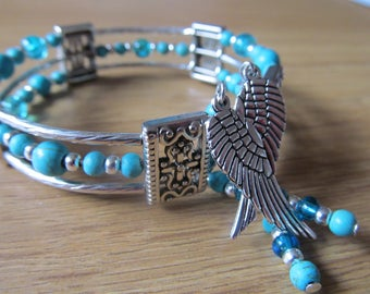 Triple loop Egyptian  cuff bracelet . Blue turquoise memory wire bangle with wing charms