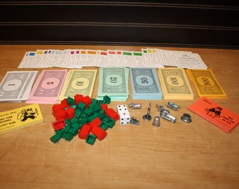 Monopoly game pieces - houses, game pieces, money, property deeds, and cards - item #2911