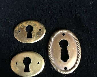 Set of three antique brass key hole covers.