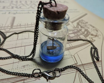 Sloop ship in a bottle necklace, sailing on a blue sea