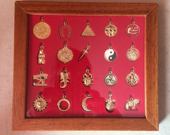 set of 20 gold enamelled metal talisman symbols pendants charms in a display case mystic good luck amulets