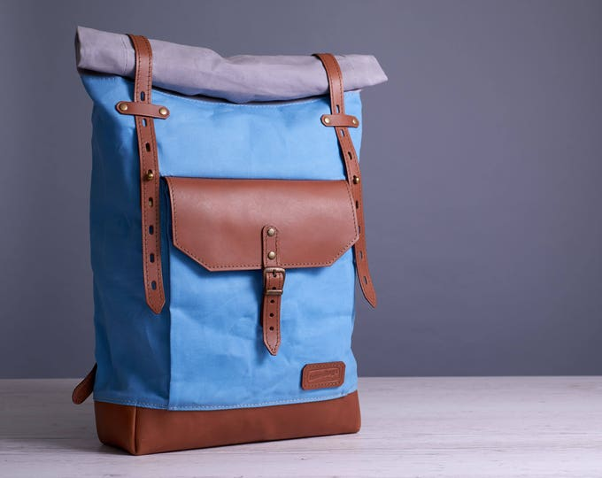 Light blue roll-top backpack. Waxed canvas and leather bag.