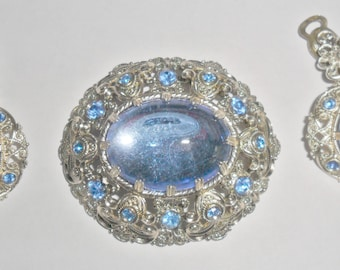 Beautiful ornate lightweight vintage West Germany goldtone blue plastic inset brooch and clipback earrings set with blue rhinestone accents
