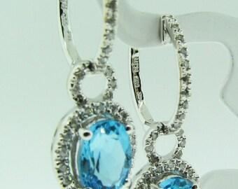 14 K white gold, Blue Topaz and diamond halo dangle earrings.
