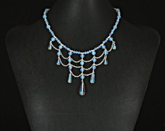 Classic Victorian drape necklace in opal glass with matching earrings by Sylvan Creations.