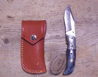 Damascus steel folding knife with thumb stud and bone handle.