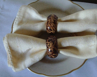 Set of four napkin rings vinegar painted in tortoise shell.