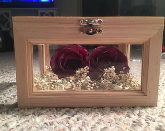 Preserved flowers in wooden shadow box.