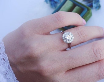 Round cut halo set engagement ring with high polished shoulders