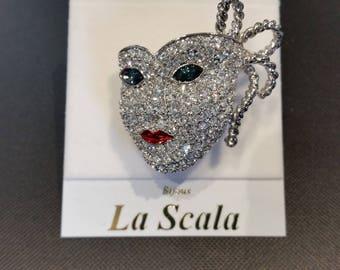 La Scala Theatre Mask brooch.  Rhodium plated with Swarovski handset Swarovski crystals.  Sapphire eyes, ruby lips.  New, Carded