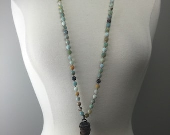 Hand knotted beaded necklace with soldered horn wrapped in leather