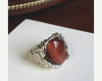 End of May Sale Beautiful Red Tigereye Cabochon stone set in a traditional Pharoah Ring wrap of sterlingt silver.  Size seven and one-half.