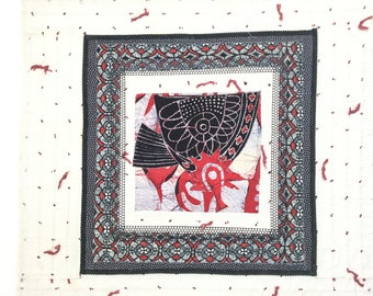 36x36 vintage fabric collage-white boarder with black,red,white,fabrics surround-striking look-light weight-easy to hang-hanging clips too.
