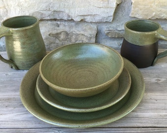 Two 4 pc pottery dinnerware place settings on dark clay