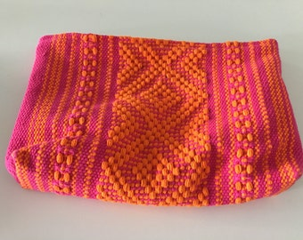 Woven pink and orange zippered clutch.  Floral fabric lined.