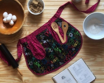 Vintage style cotton half apron. Peace and Love pop off this black background with peace signs all around in pink.