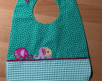 Green bib with elephant patterns embroidered, embellished with piping