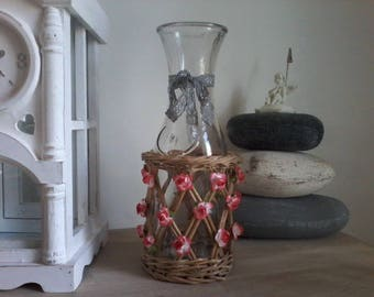 Glass decanter in a wicker basket, vintage bottle