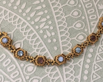 Vintage Bracelet with 7 jewels or sets in it.  Gold Color with Stones set in it.  Very pretty