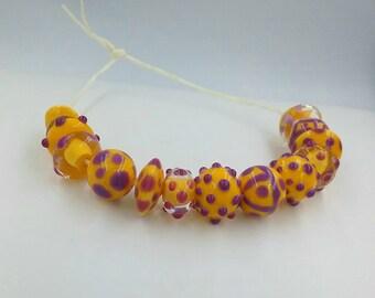 13 yellow Italian glass beads with purple decoration.