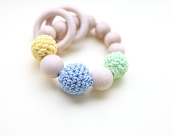 Light green, yellow and blue teething ring toy with crochet wooden beads. Rattle for baby.