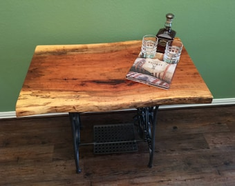 Live-edge slab table with antique sewing machine base