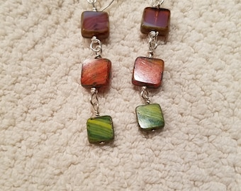 Dangle earrings featuring purple, orange and green stained glass square beads on silver ear wires