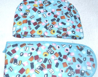 Liquorice Allsorts tossed on pale blue Tea cosy and Oven gloves