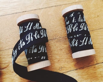 screenprinted spool of ribbon with calligraphed alphabet