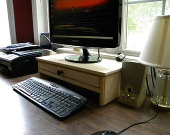 Computer monitor stand with drawer for extra storage and hidden hole in drawer back for cell phone chargers