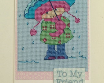 Cross stitch friendship card of a girl standing in the rain under her umbrella and the wording 'To my Friend'