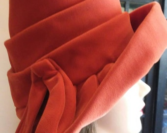 Vintage Burnt orange cloche-style hat with large brim and fabric bow.