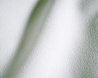 Mirella Crepe White fabric 100% Polyester with a great lightweight drape. White solid color fabric.  Purchase by 1/2 meter