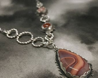 Banded agate and sterling silver window necklace, asymmetrical design, accented with carnelian and pink moonstone, one of a kind design