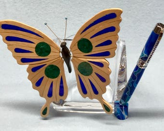 Acrylic pen holder with decorative intarsia butterfly and pen.