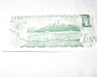 Vintage Canadian one dollar bill from 1973 has been circulated but is in great condition.