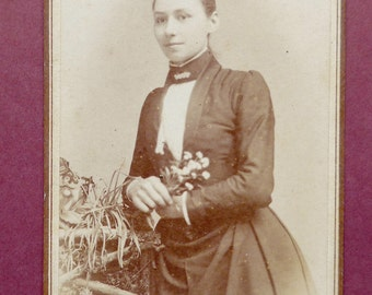 Carte-de-visite, antique, a lady holding a spry of flowers.  T.H. Winterbourn, Waterloo House, Leominster.  Blank reverse.  c1890.