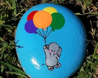 Cute blushing elephant floating with balloons painted rock