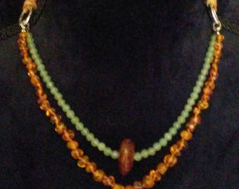 Amber beads on hand knotted silk, green aventurine, deerskin lace.