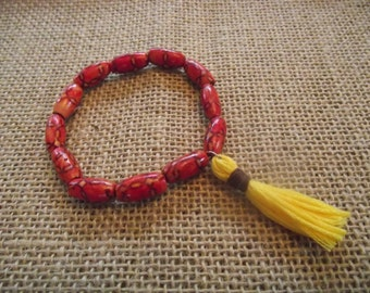 Patterned wood bead bracelet with yellow tassel